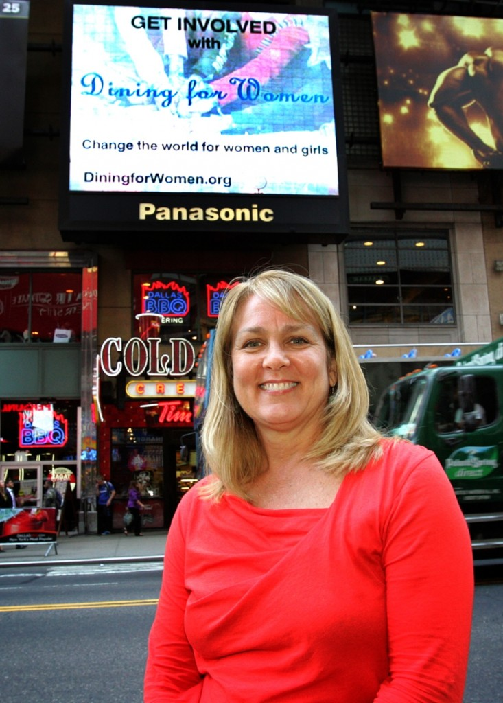 Marsha Wallace, DFW Founder, in front of our video in Times Square
