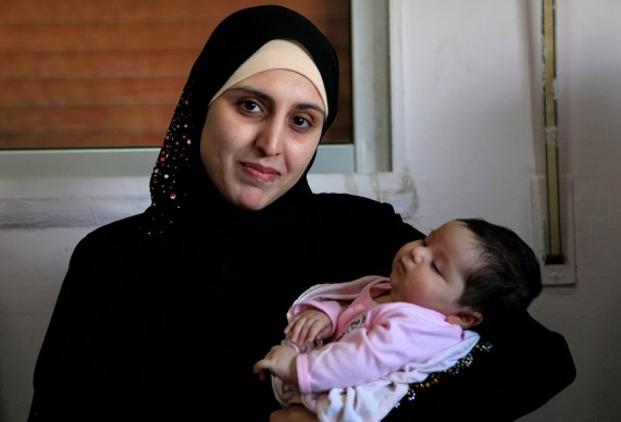 A_Syrian_refugee_and_her_newborn_baby_at_a_clinic_in_Ramtha,_Jordan_(9613483141)