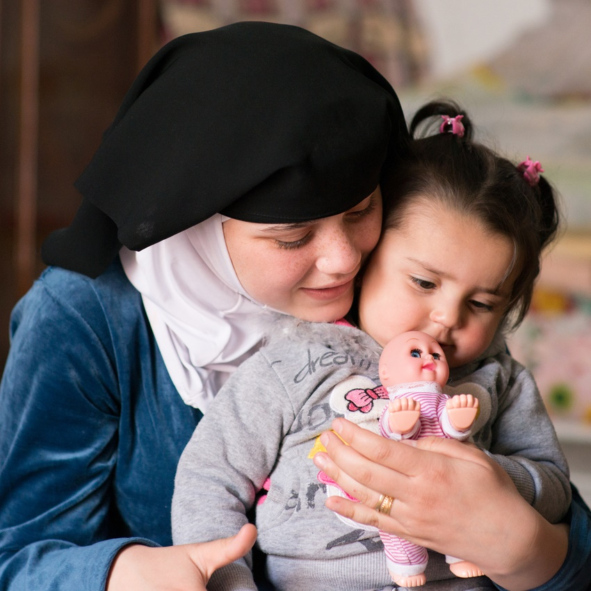 """On 13 February 2016 in Jordan, a refugee from the Syrian Arab Republic, Qamar, is 14 years old. Raneem, 1, sits on her mother's lap. Qamar married 2 years ago in Ramtha, Jordan where she now lives, having fled Syria after the conflict began. """"We're lucky,"""" says Qamar, """"Its safer here than in Syria but I feel trapped in this house as there's not enough room for all of us."""" Qamar feels a huge sense of responsibility being a mother. """"I was a child when I married and now I'm a child, with a child,"""" she says. Qamar can't read or write and has not attended school since her family fled their home country."""