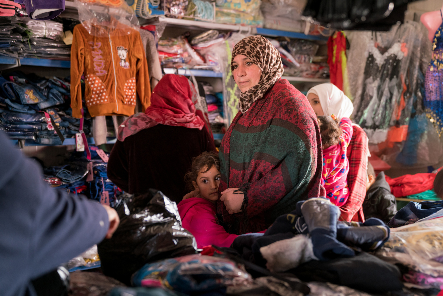 Manar, 34 years old, buying winter clothes for her children at a shop in Za'atari camp with the cash support from UNICEF.